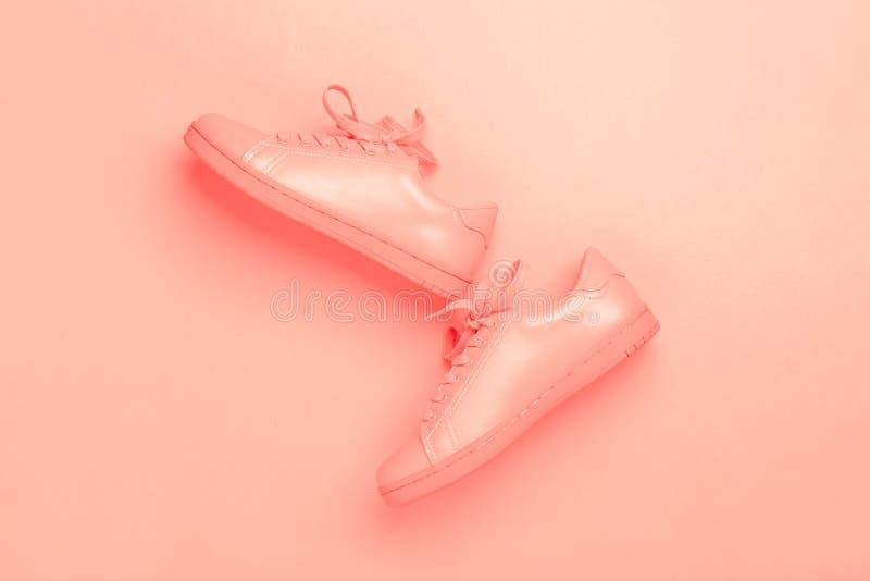 Un par de zapatos coralinos en el fondo coralino imagen de archivo