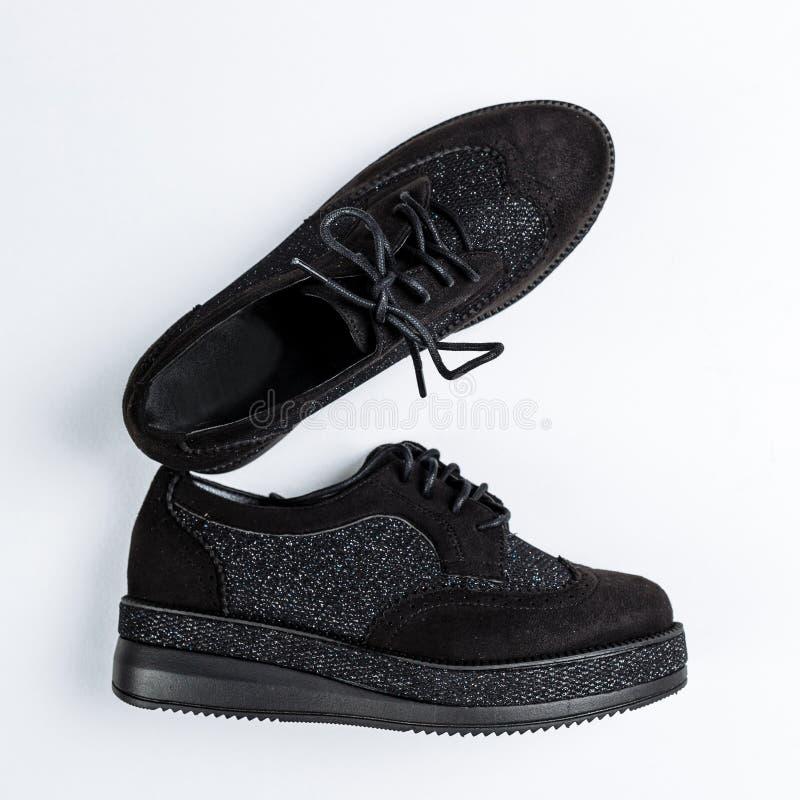 Un par de zapatos negros con los partes movibles brillantes en lenguados gruesos en un fondo blanco fotografía de archivo