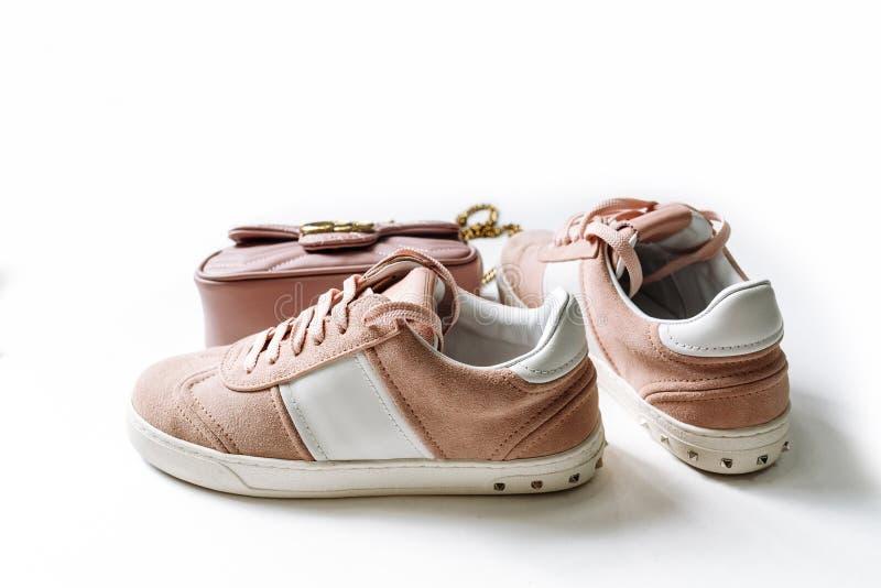 Un par de zapatos rosados del ante con los acentos blancos y de un bolso en el fondo en un fondo blanco imagen de archivo libre de regalías