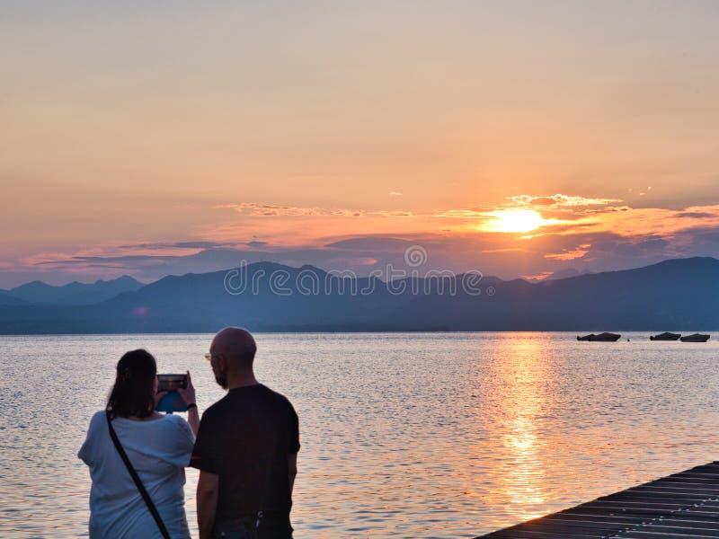 Un par disfruta y fotografía con un teléfono celular de la puesta del sol sobre el lago Garda de la orilla de la ciudad de Bardol fotografía de archivo