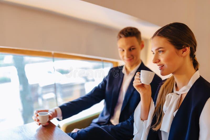 Un par elegante bebe el café de la mañana en el café, los hombres de negocios jovenes y los freelancers fotografía de archivo