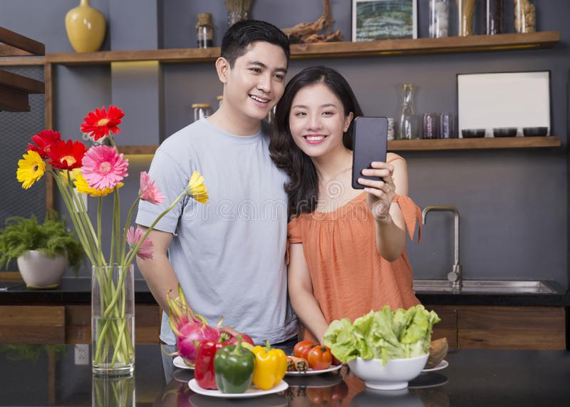 Un par en la cocina con mucha fruta y verdura imagen de archivo libre de regalías