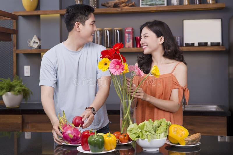 Un par en la cocina con mucha fruta y verdura imágenes de archivo libres de regalías