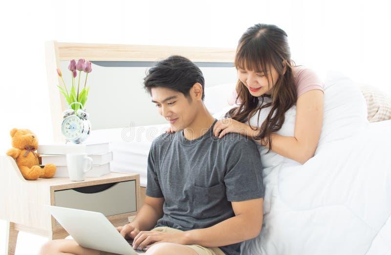 Un par está buscando Internet en dormitorio foto de archivo