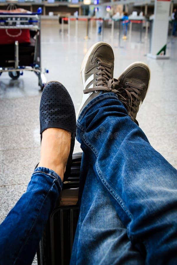 Un par está esperando en el aeropuerto con sus pies en el suitca fotos de archivo libres de regalías