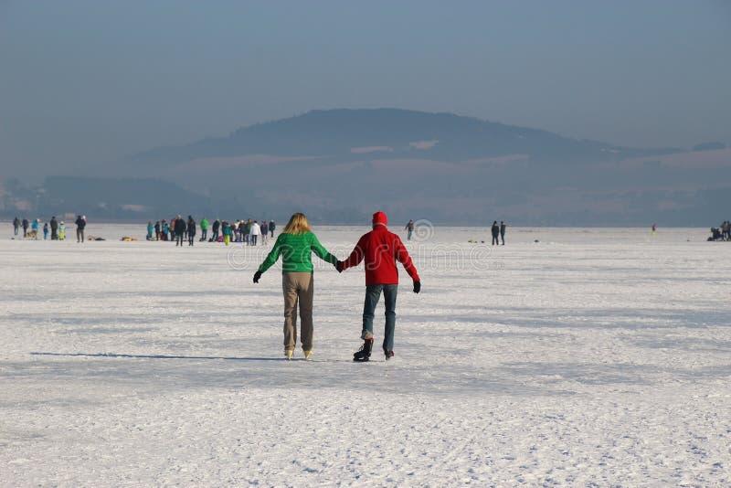 Un par está patinando en el hielo de un lago congelado Seekirchen, Austria imagen de archivo libre de regalías