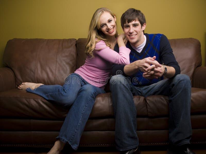 Un par feliz abraza en el sofá foto de archivo