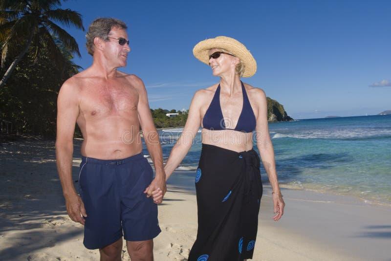 Un par feliz que recorre en la playa foto de archivo libre de regalías