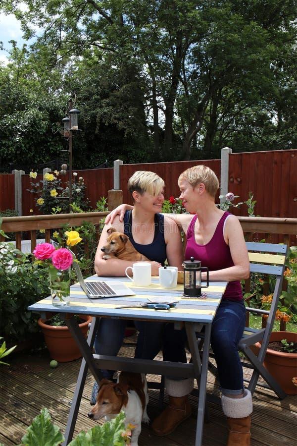 Un par gay feliz en casa en el jardín, abrazando imagenes de archivo