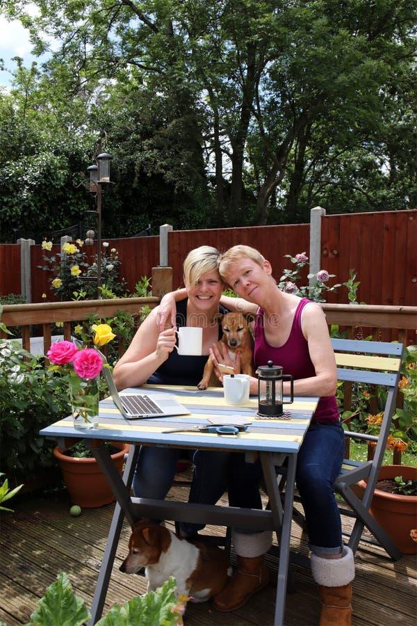 Un par gay feliz en casa en el jardín, abrazando fotos de archivo