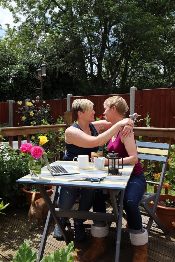 Un par gay feliz en casa en el jardín, abrazando imagen de archivo libre de regalías