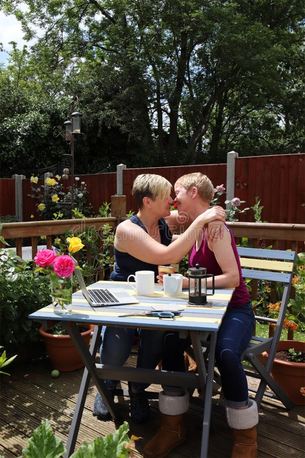 Un par gay feliz en casa en el jardín, besándose y abrazando imagen de archivo libre de regalías