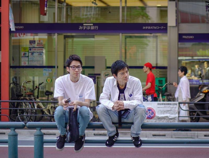 Un par gay que se sienta en la calle de Tokio foto de archivo libre de regalías