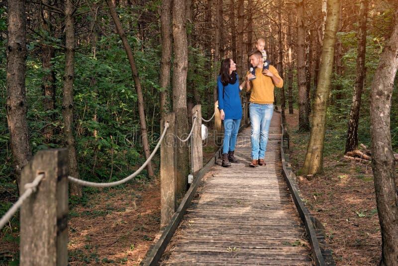 Un par joven camina en el bosque con un niño pequeño fotografía de archivo libre de regalías