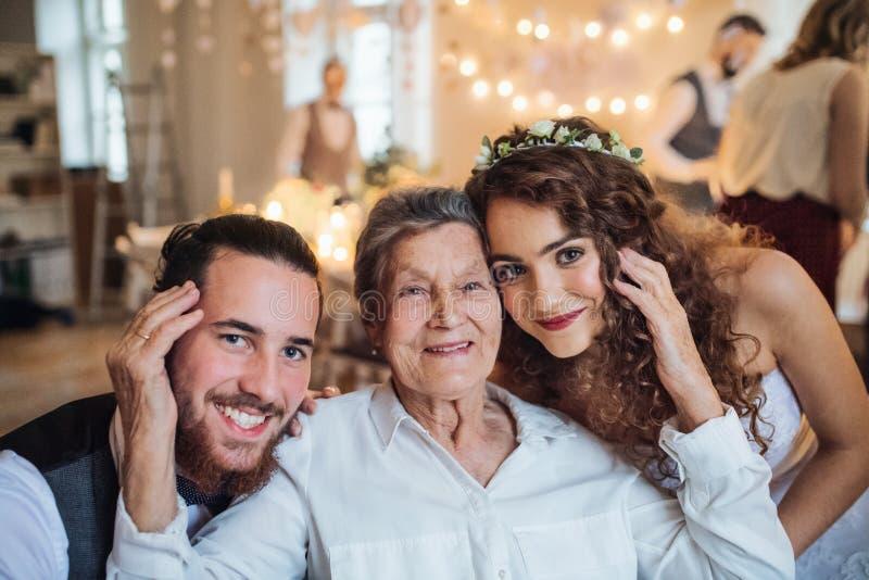 Un par joven con la abuela en una boda, mirando la cámara fotografía de archivo