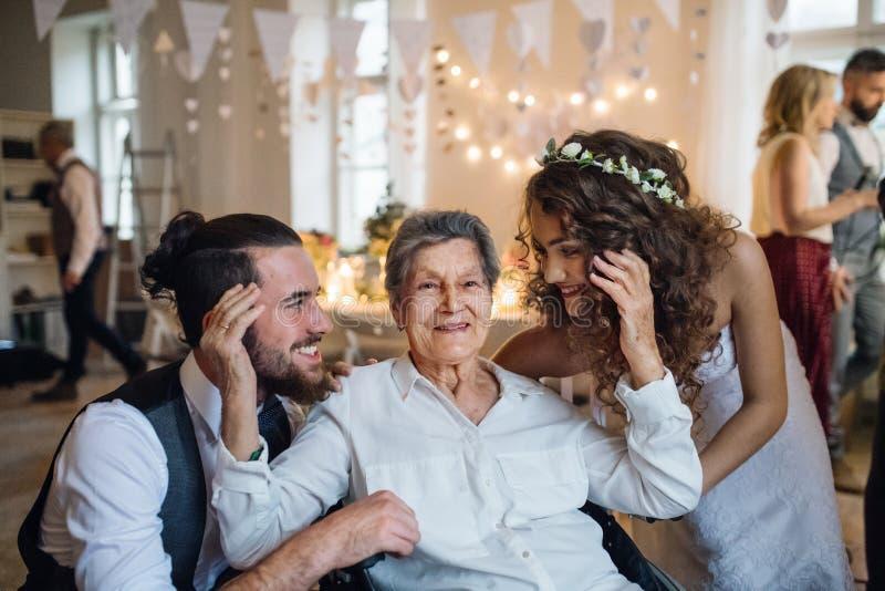 Un par joven con la abuela en una boda, presentando para una fotografía foto de archivo libre de regalías