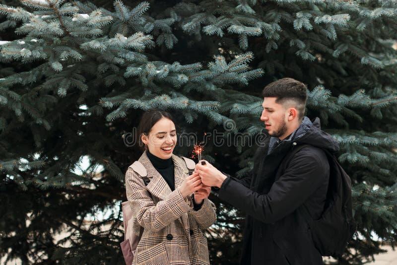 Un par joven con las bengalas en las manos en el parque de la ciudad imagen de archivo