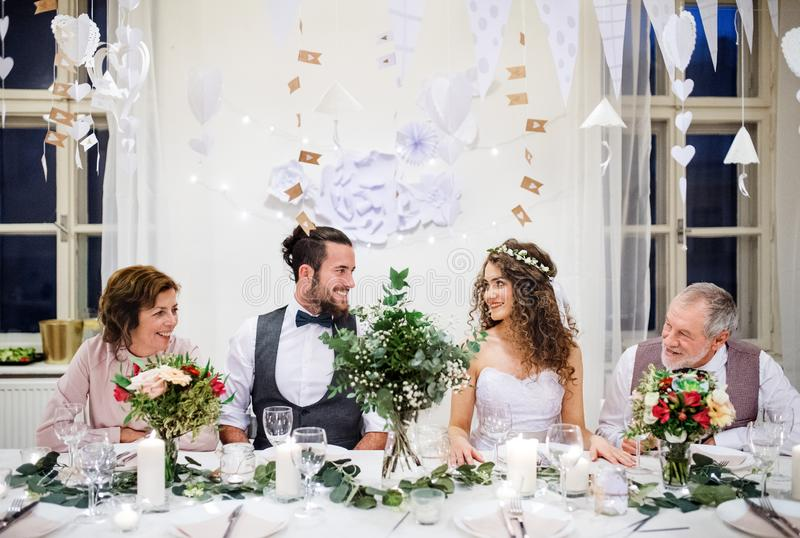 Un par joven con los padres que se sientan en una tabla en una boda, mirando uno a fotos de archivo