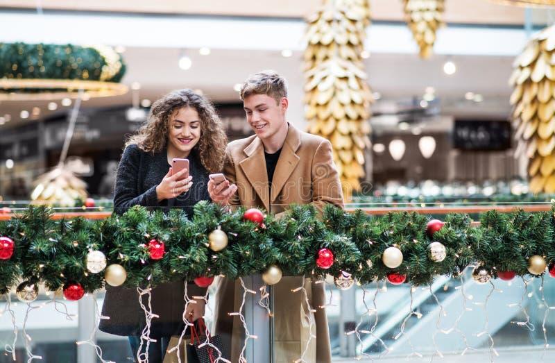 Un par joven con smartphone en centro comercial en la Navidad fotos de archivo