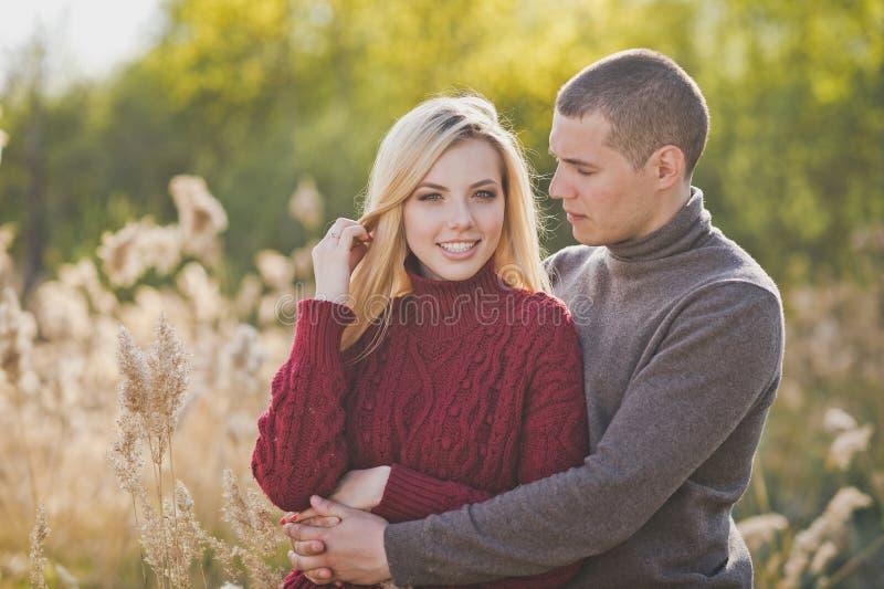Un par joven en el amor que abraza contra la perspectiva de las cañas 1351 foto de archivo libre de regalías