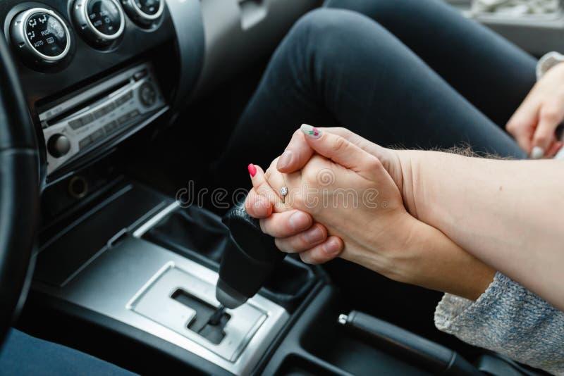 Un par joven en el amor que lleva a cabo las manos, sosteniendo encendido la palanca del cambio que entra el viaje por carretera  fotos de archivo libres de regalías