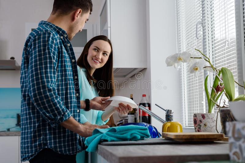 Un par joven en la cocina junto para lavar y para limpiar los platos, una visión inferior y una vista lateral, la alegría de la v fotografía de archivo