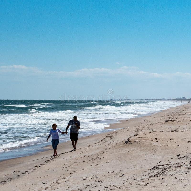 Un par joven en la playa foto de archivo
