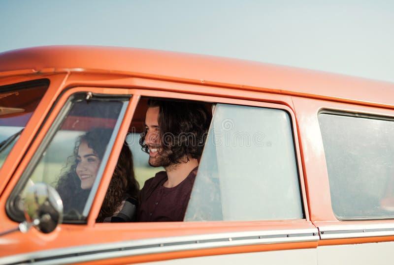 Un par joven en un roadtrip a través del campo, conduciendo el minivan fotografía de archivo