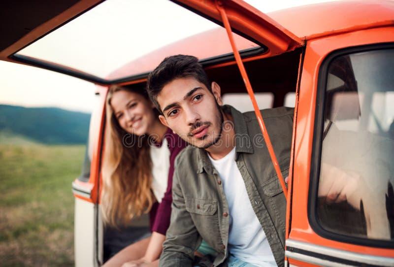 Un par joven en un roadtrip a través del campo, sentándose en minivan imagen de archivo