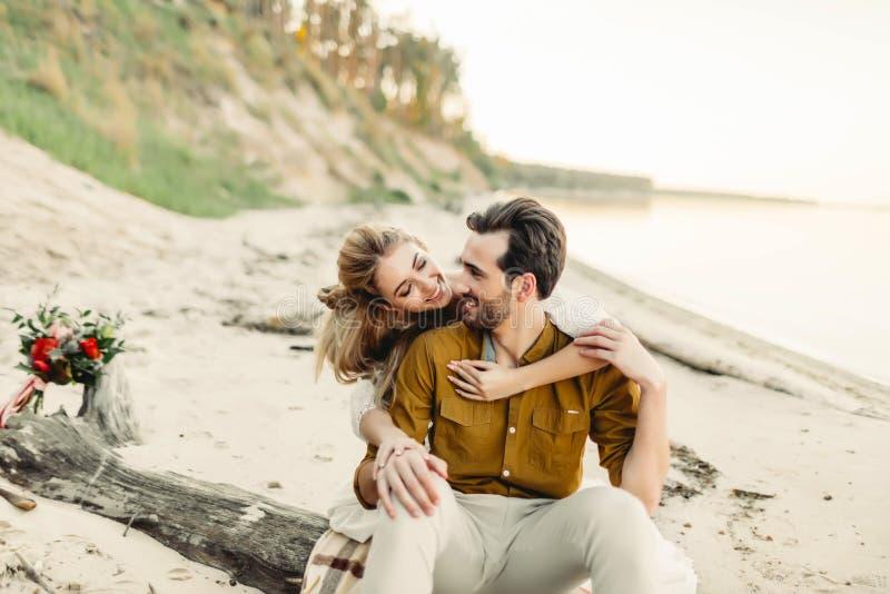 Un par joven es sonriente y de abrazo en la playa Ceremonia de boda rústica al aire libre La novia y el novio miran uno a fotos de archivo