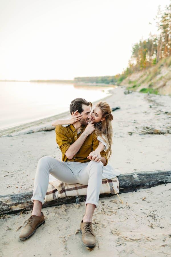 Un par joven está abrazando en la playa La muchacha hermosa abraza a su novio de la parte posterior Caminata Wedding Los recienes fotos de archivo