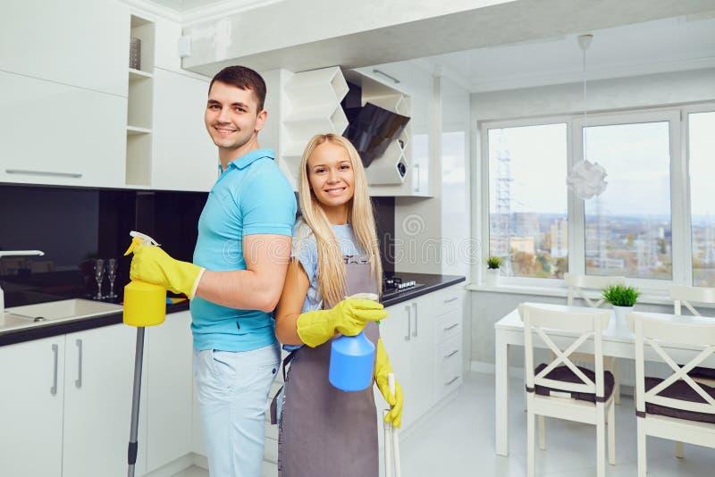 Un par joven está limpiando un apartamento foto de archivo