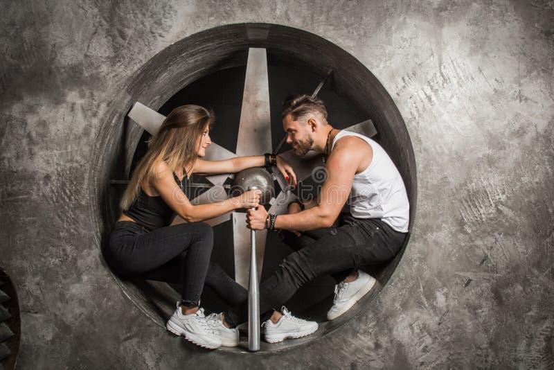 Un par joven un hombre y una mujer con una mirada juguetona del humor, de moda y deportiva se sienta cerca de una fan industrial  fotos de archivo