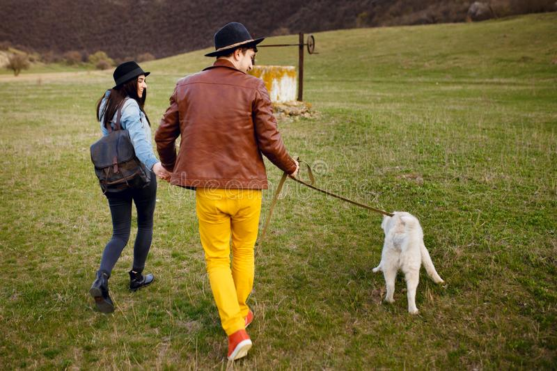 Un par joven pasar el tiempo junto exterior con su perro fornido Forma de vida romántica del concepto imagen de archivo libre de regalías
