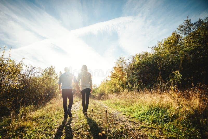 Un par joven que camina al aire libre llevando a cabo las manos foto de archivo libre de regalías