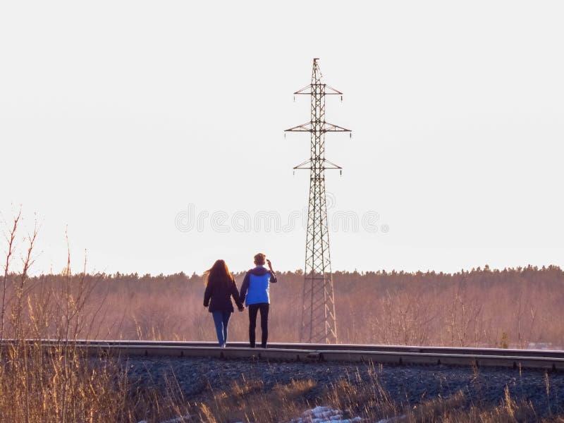Un par joven que camina a lo largo del ferrocarril con el bosque grueso en el fondo fotografía de archivo libre de regalías