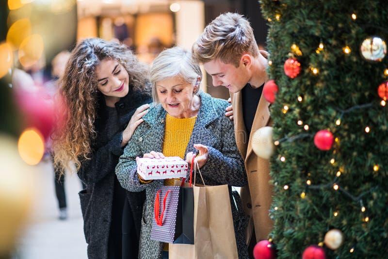 Un par joven que da un presente a la abuela en centro comercial en la Navidad imagen de archivo libre de regalías