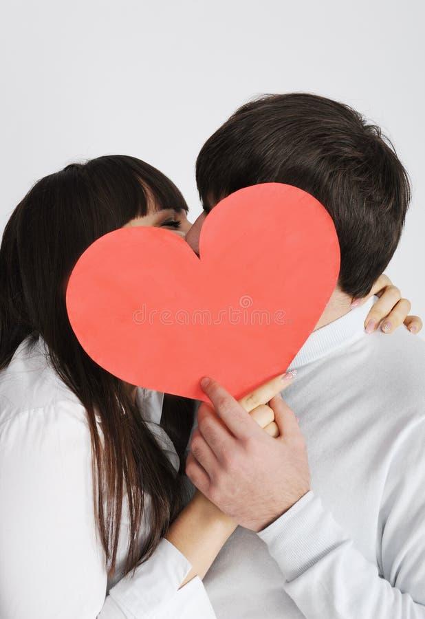 Un par joven que se besa detrás de símbolo del amor fotografía de archivo