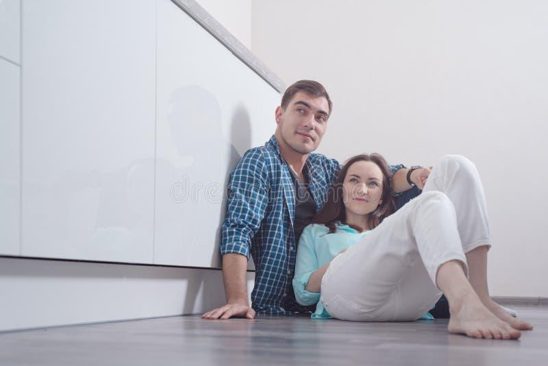 Un par joven que se sienta en el piso de entarimado dentro de una cocina blanca y que mira al lado, una copia del espacio imagen de archivo