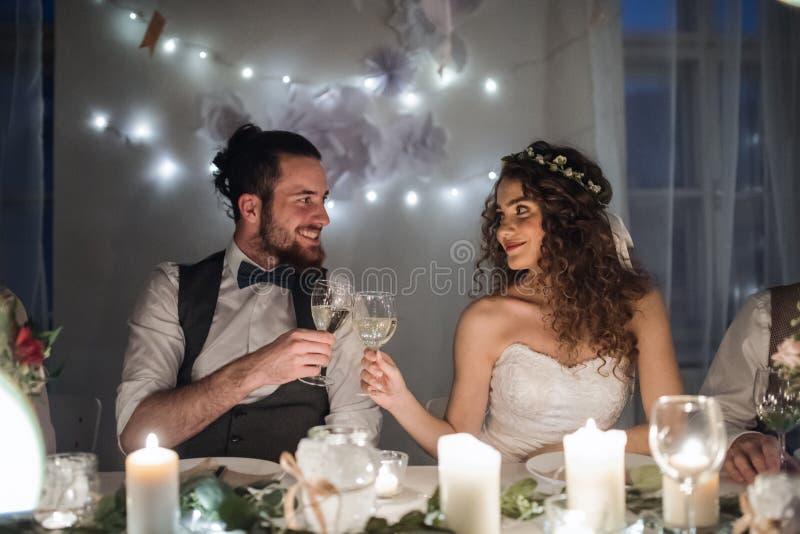 Un par joven que se sienta en una tabla en una boda, vidrios que tintinean imagen de archivo libre de regalías