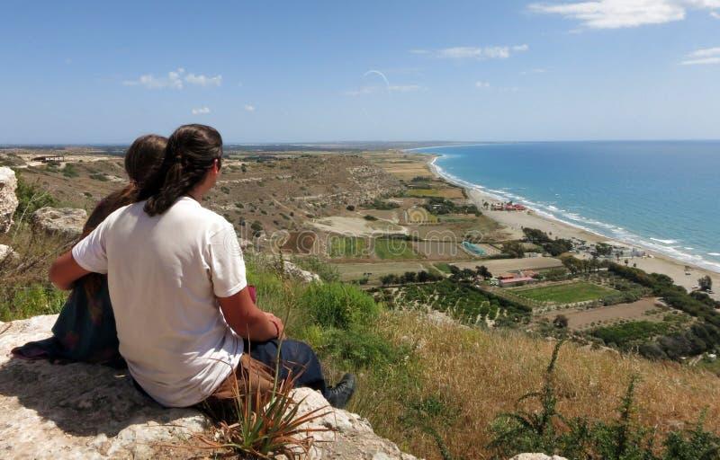Un par joven que se sienta encima de un acantilado que mira el mar Mediterr?neo fotografía de archivo