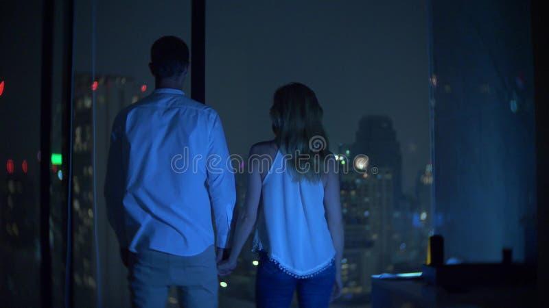 Un par joven se coloca en el fondo de una ventana panorámica que pasa por alto la ciudad Noche de la tarde Falta de definición de imágenes de archivo libres de regalías