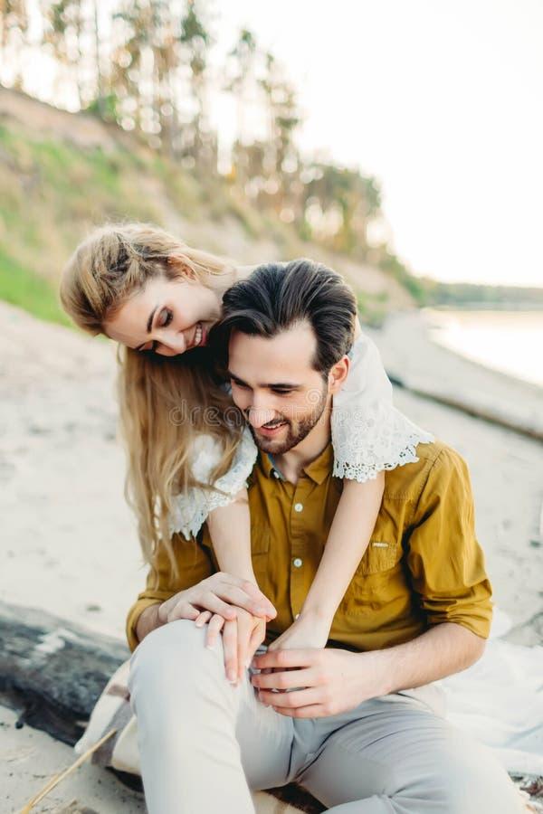 Un par joven se está divirtiendo y está abrazando en la playa La muchacha hermosa abraza a su novio de la parte posterior boda il imagenes de archivo