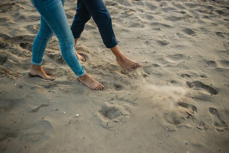 Un par joven se está divirtiendo y está caminando en la costa costa del mar Las piernas se cierran para arriba Fecha romántica en foto de archivo libre de regalías