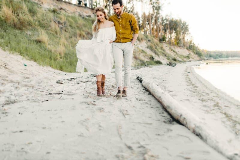 Un par joven se está divirtiendo y está caminando en la costa costa del mar Recienes casados que miran uno a con dulzura romántic fotos de archivo libres de regalías