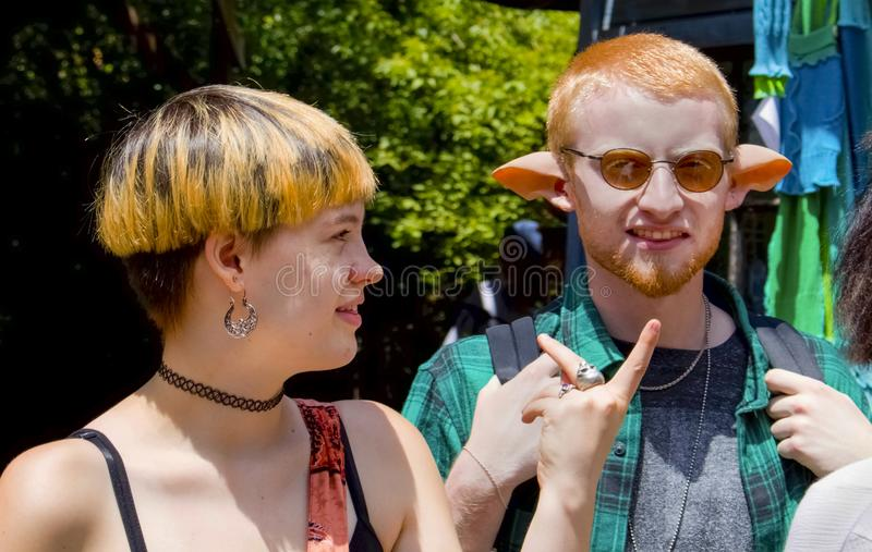 Un par joven se vistió para arriba en trajes de la fantasía - él lleva los oídos artificiales del duende o del centauro fotos de archivo
