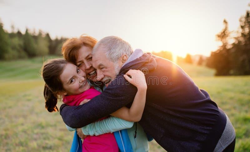 Un par mayor activo con la situación de la nieta en naturaleza en la puesta del sol imágenes de archivo libres de regalías
