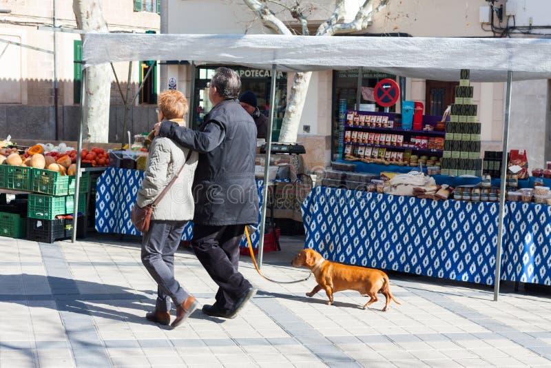 Un par mayor con un perro que camina a lo largo de las paradas en un mercado local en Esporles, Mallorca, España foto de archivo libre de regalías