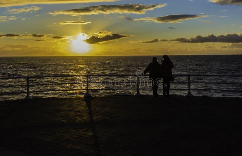Un par mira la puesta del sol imagen de archivo