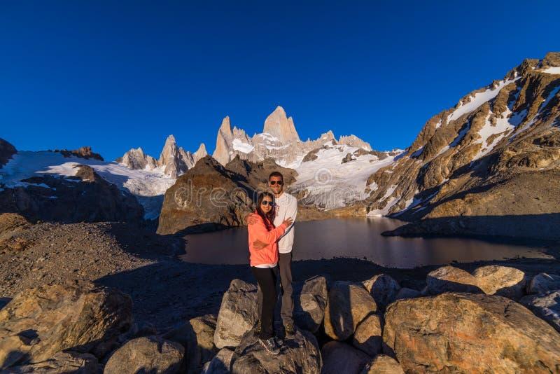 Un par presenta debajo del Mt Fitz Roy Un pico rugoso en la Patagonia, la Argentina fotos de archivo
